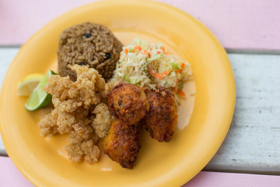 yellow plate with coleslaw, cracked conch, conch fritters, and rice and peas