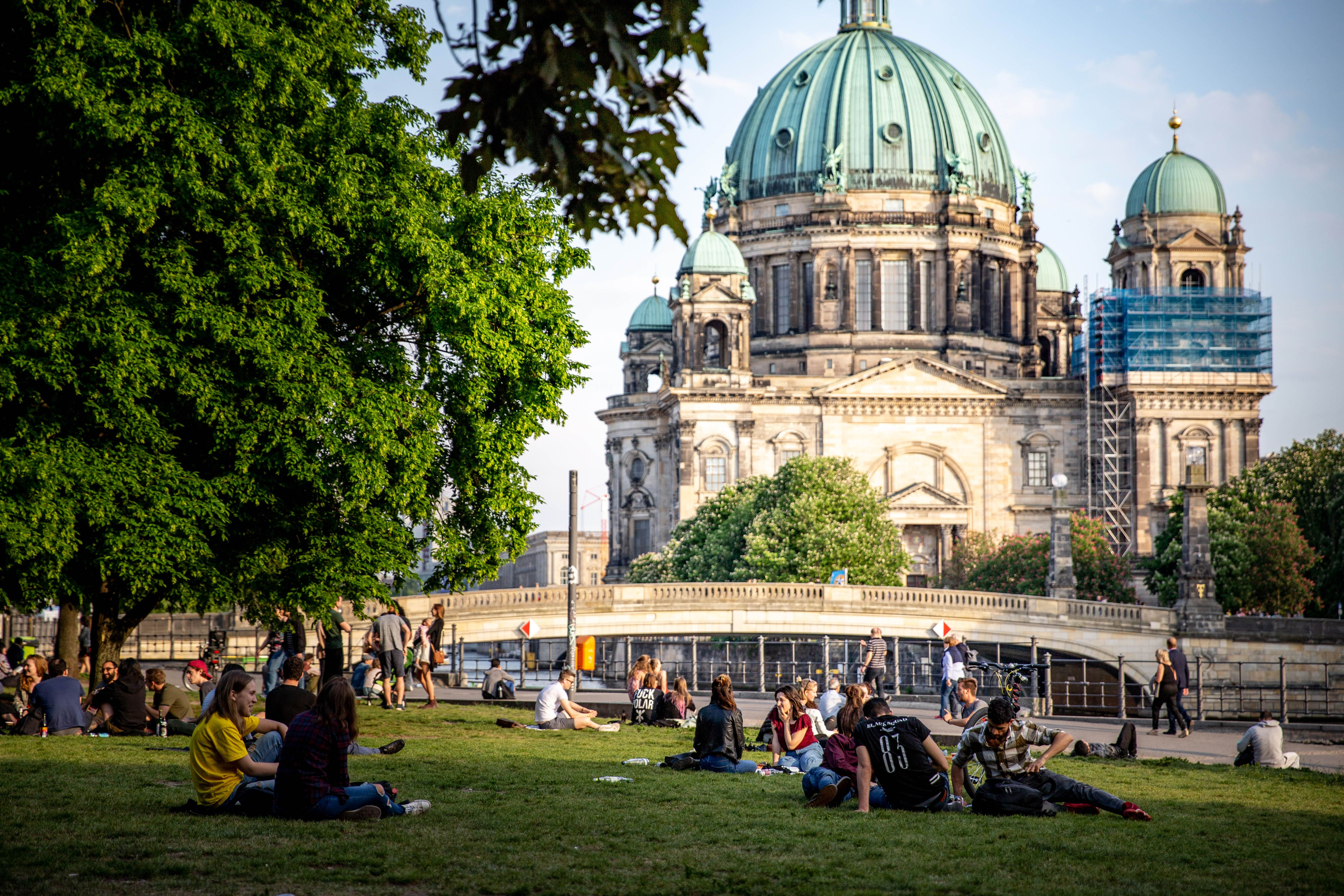 People sitting on the lawn on Museum Island in front of the Berlin Cathedral