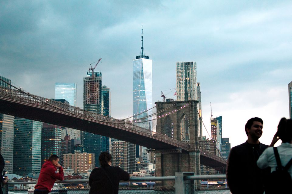 People standing observing the Brooklyn Bridge