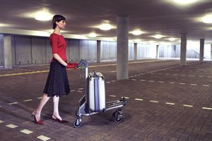 Young woman pushing luggage trolley through empty car park
