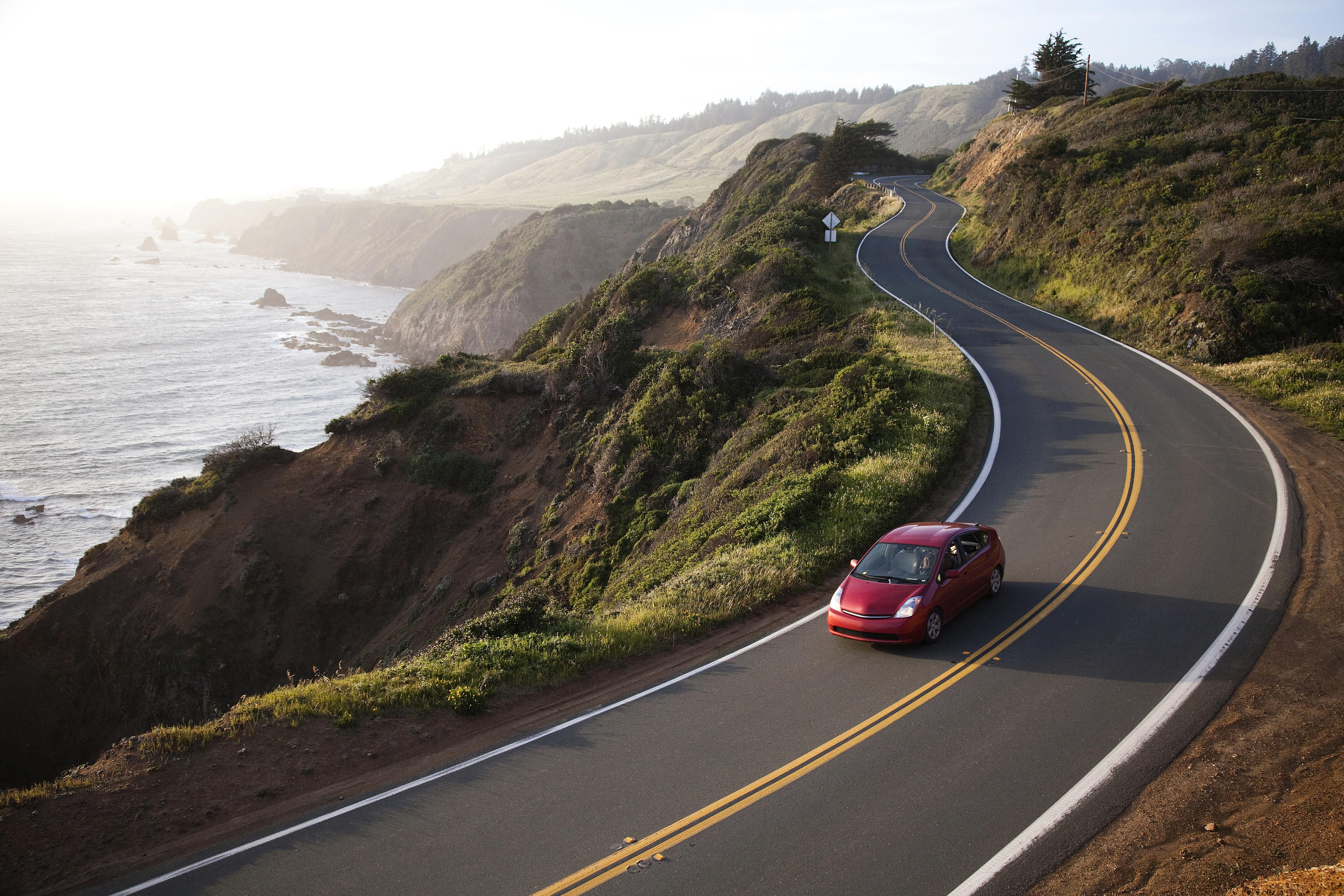 A red car drives on a highway near the Pacific Ocean.