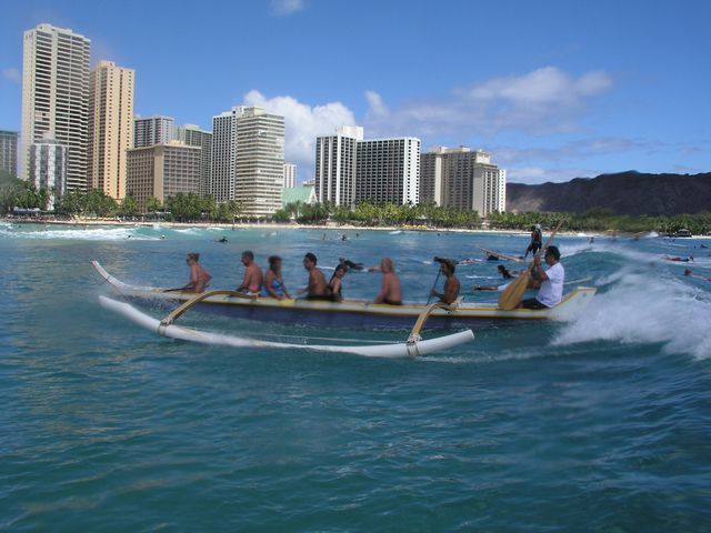 Paddling an outrigger canoe by Oahu's Waikiki beach in Hawaii