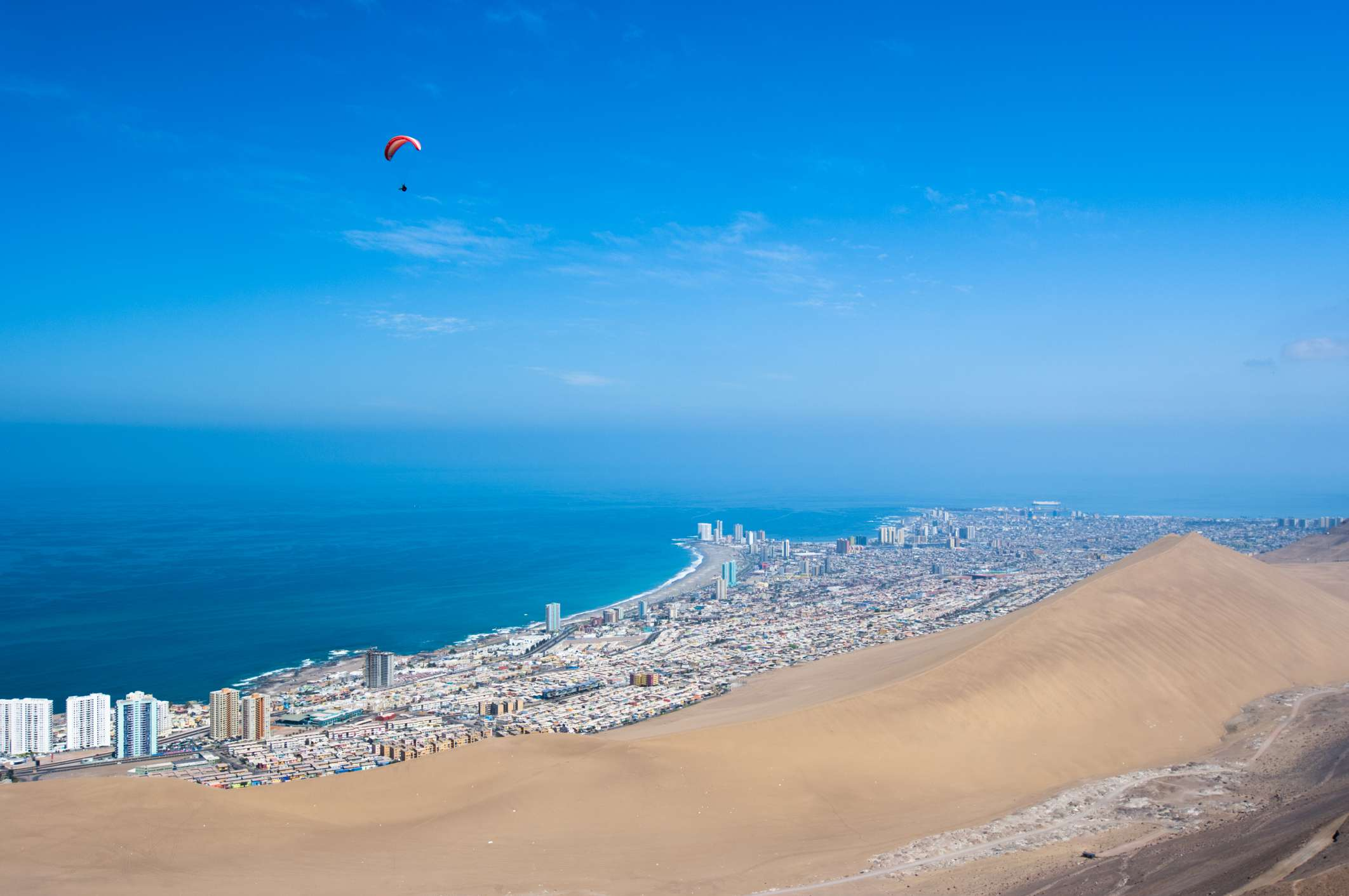 aerial shot of desert and coastal city with small paraglider in the sky
