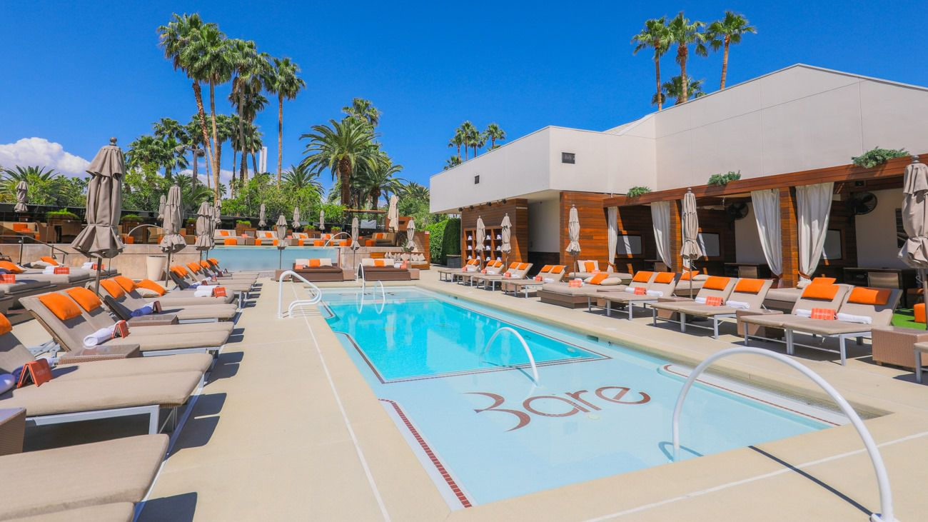 pool with tan and orange pool chairs around it