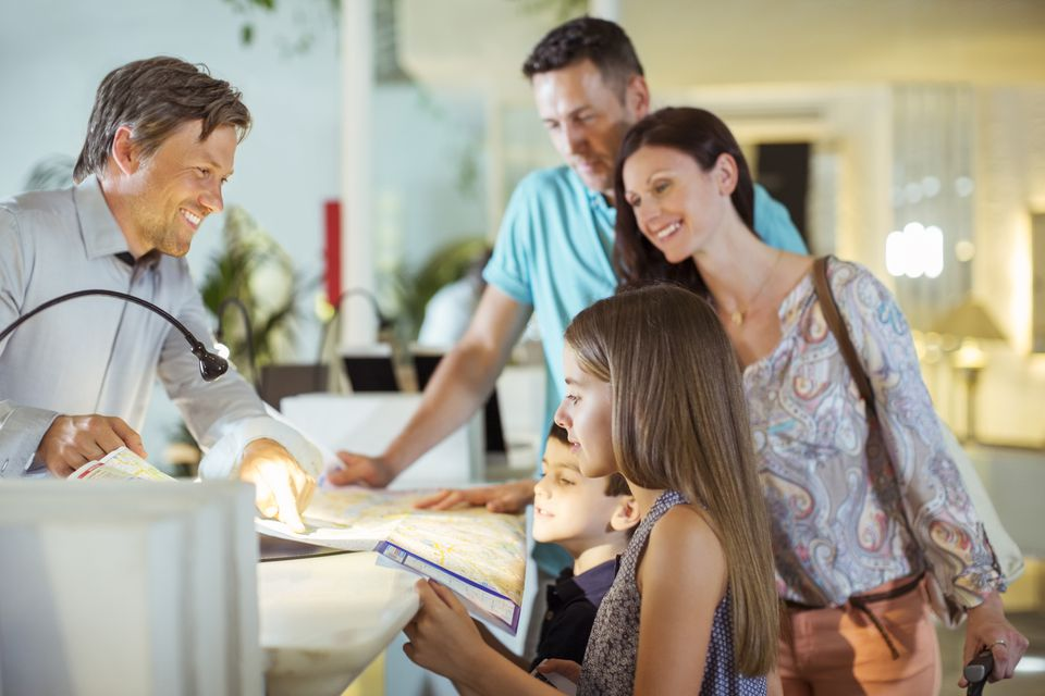 Family with two children at reception desk in hotel lobby