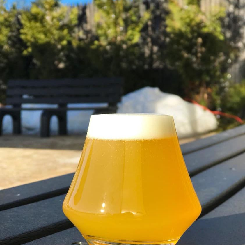 Short glass with amber-colored beer on an outdoor table at The Alchemist