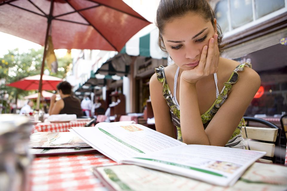 Young woman looking at menu at restaurant
