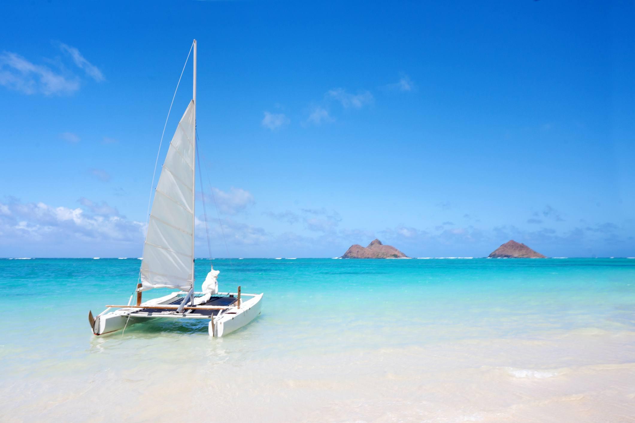 Sailboat at Lanikai Beach on beautiful day in Oahu, Hawaii.