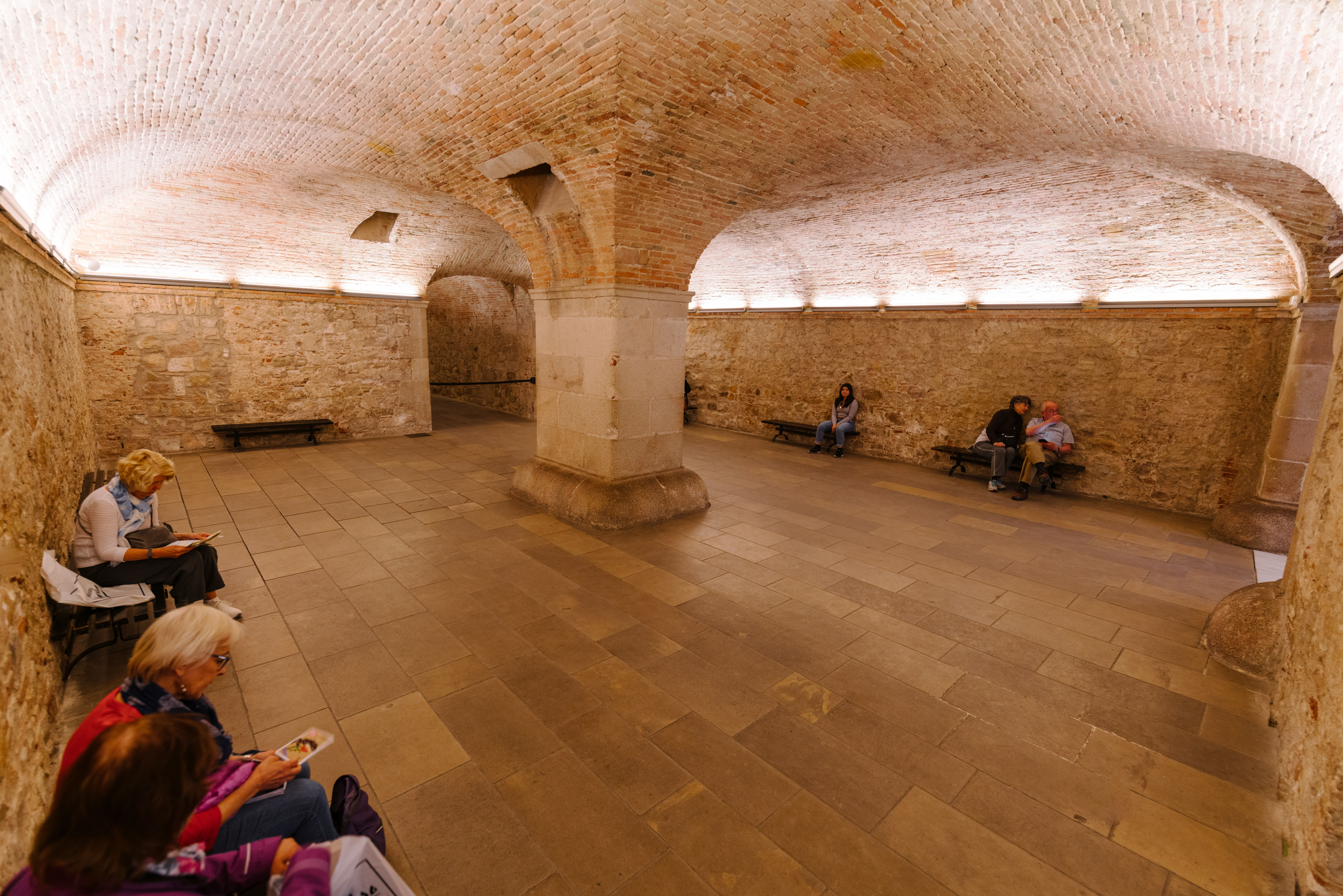 A large arched room with people sitting on the side inside the Picasso Museum