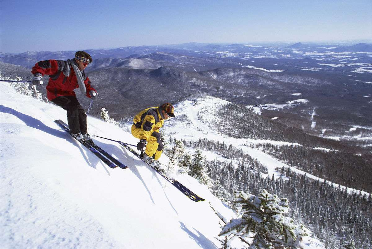 Two skiers race down the side of the mountain with stunning scenery in the background.