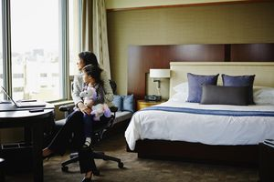 Businesswoman sitting at desk in hotel room with daughter on lap looking out window