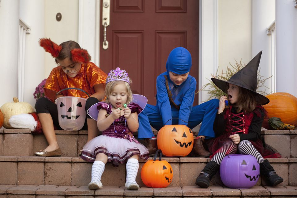 Kids enjoying Halloween candy while dressed in their Halloween costumes.