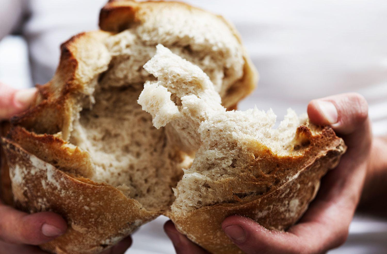 manos que separan una barra de pan