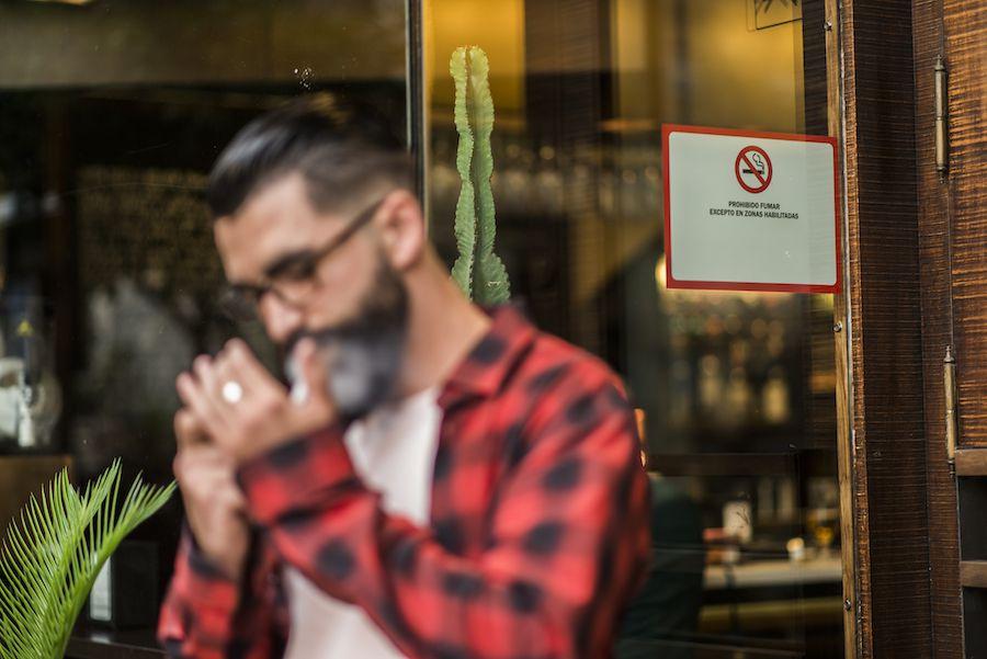 Hombre fumando en el bar con prohibición de fumar
