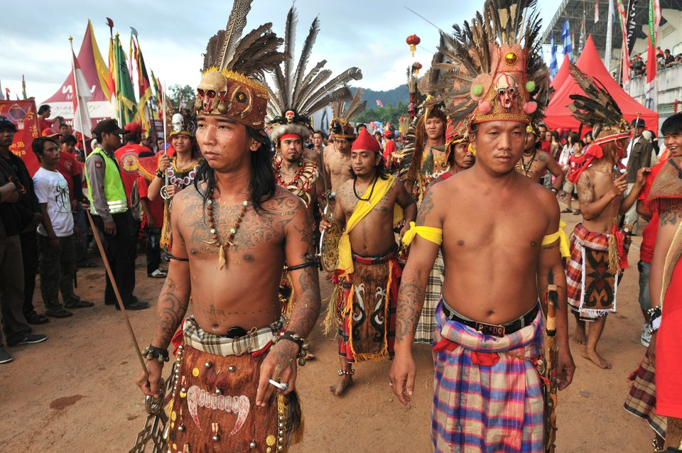 Dayak people in traditional garb walk for Gawai Dayak
