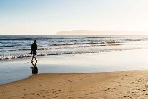 A man walking along the beach