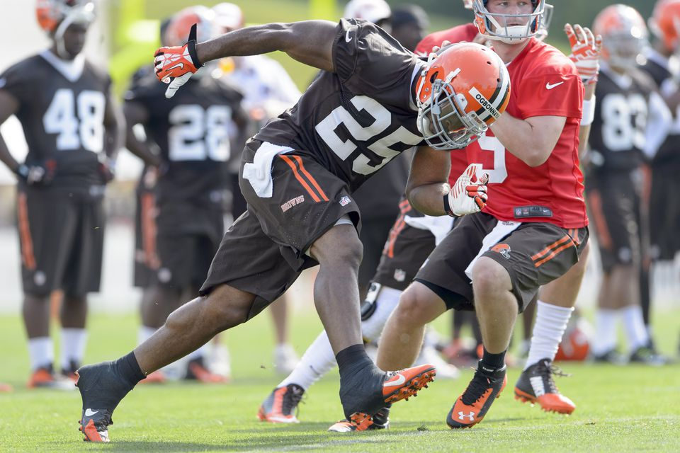 One Cleveland Browns player running past another on the field