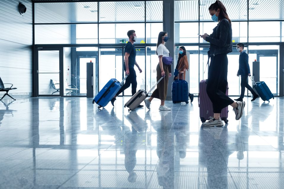 Passengers at the airport with luggage, wearing N95 face masks