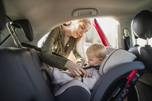 Young Mother putting her son in a car seat.
