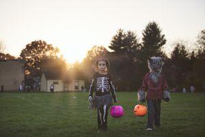 costumed children walking across grassy field