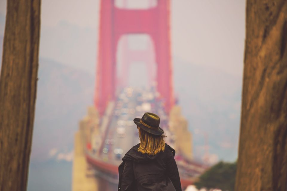 Traveler woman with the Golden Gate bridge from overlook.