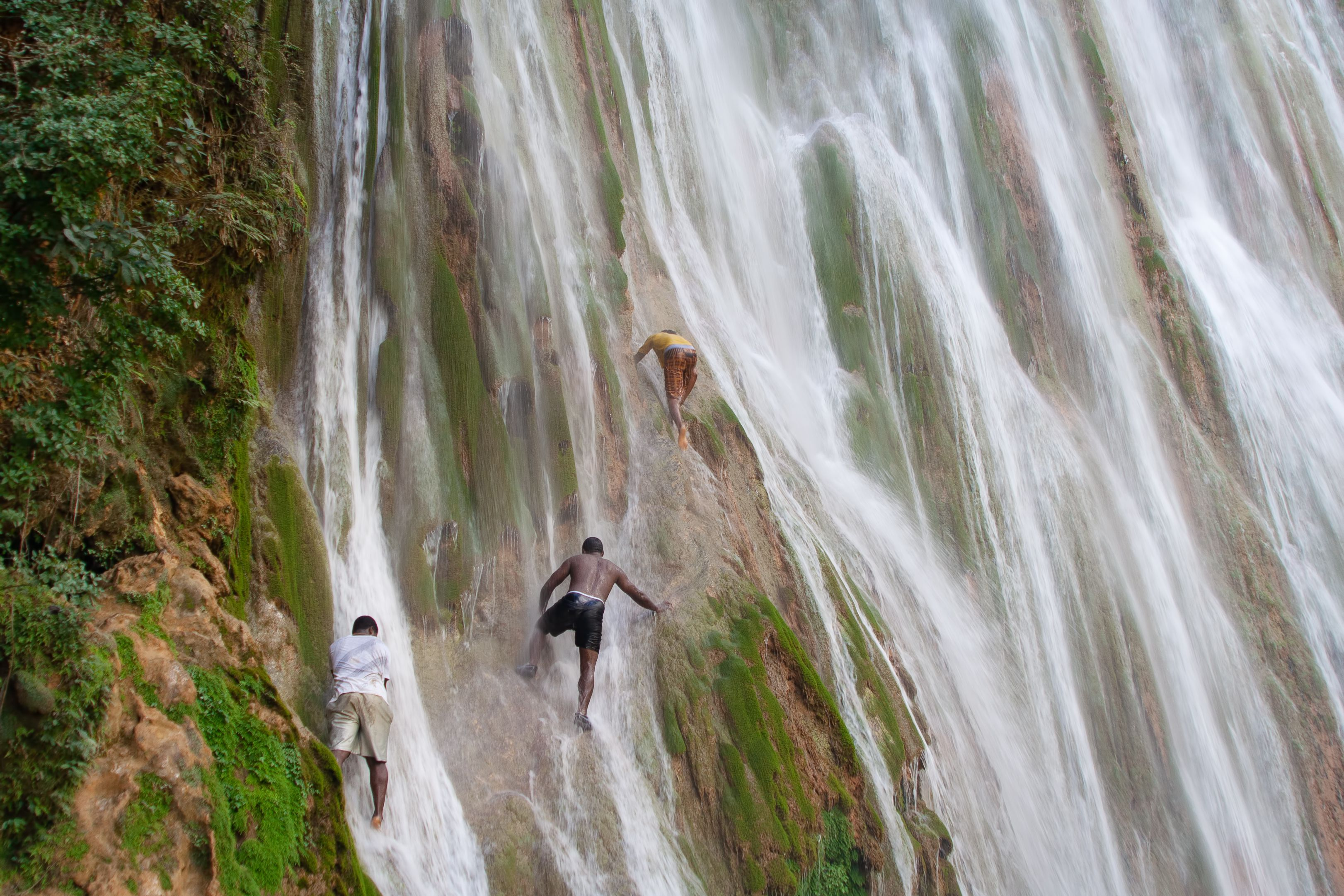 Young guys climb the ledges of a cliff on the waterfall