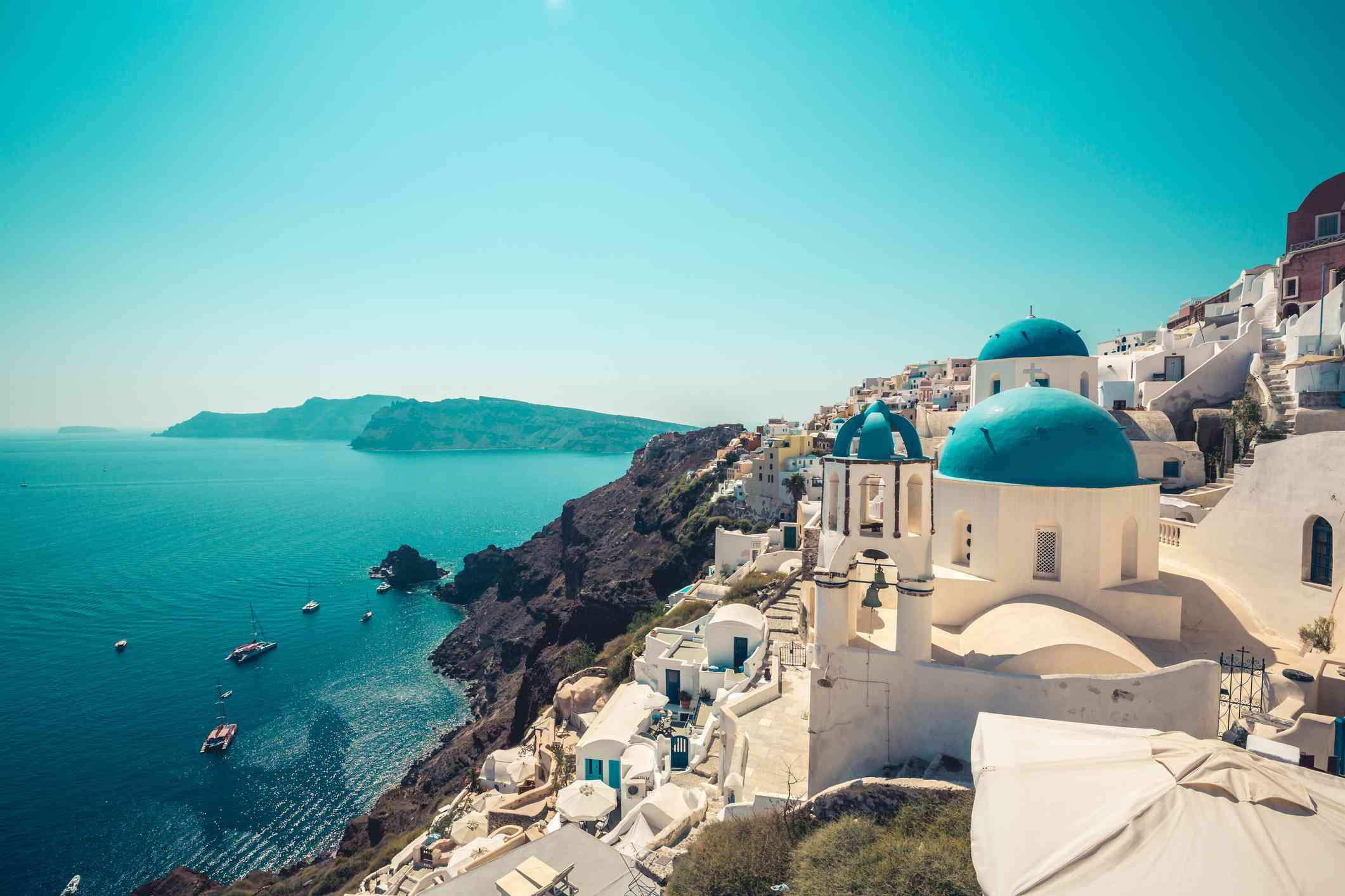 The white buildings on the cliffs of Santorini with sail boats docked below