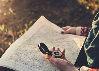 A hiker uses a map and compass to navigate