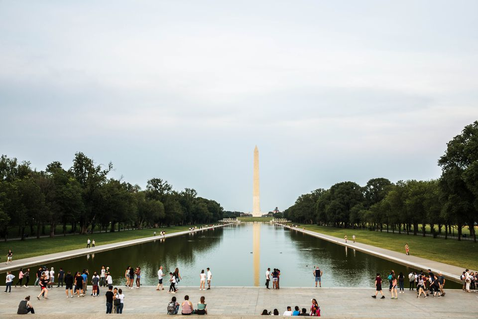 Las personas de pie alrededor de la piscina reflectante en el National Mall