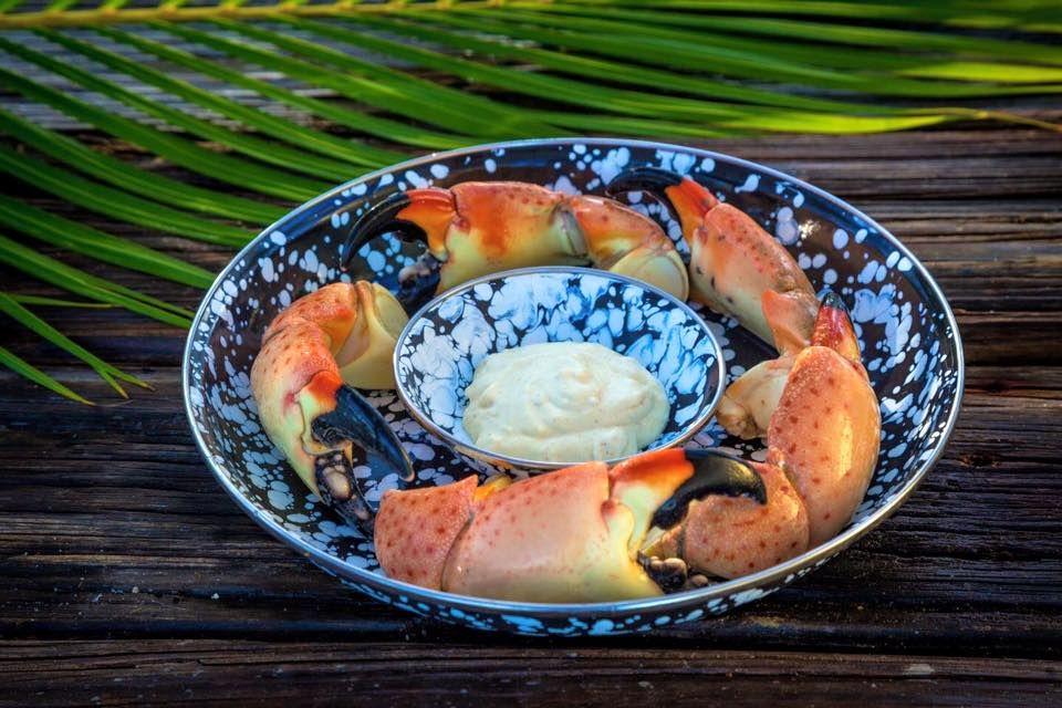 garras de cangrejo de piedra en círculo sobre un plato con un tazón de inmersión salsa en el medio