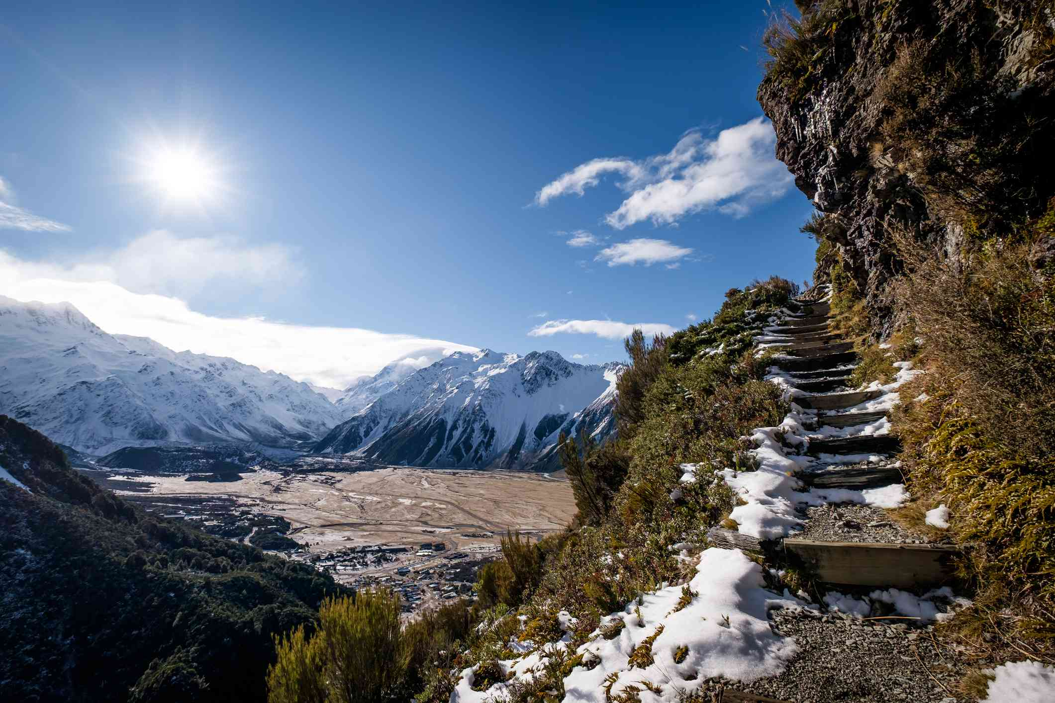 snowy mountain landscape with stone staircase beside a cliff speckled with snow