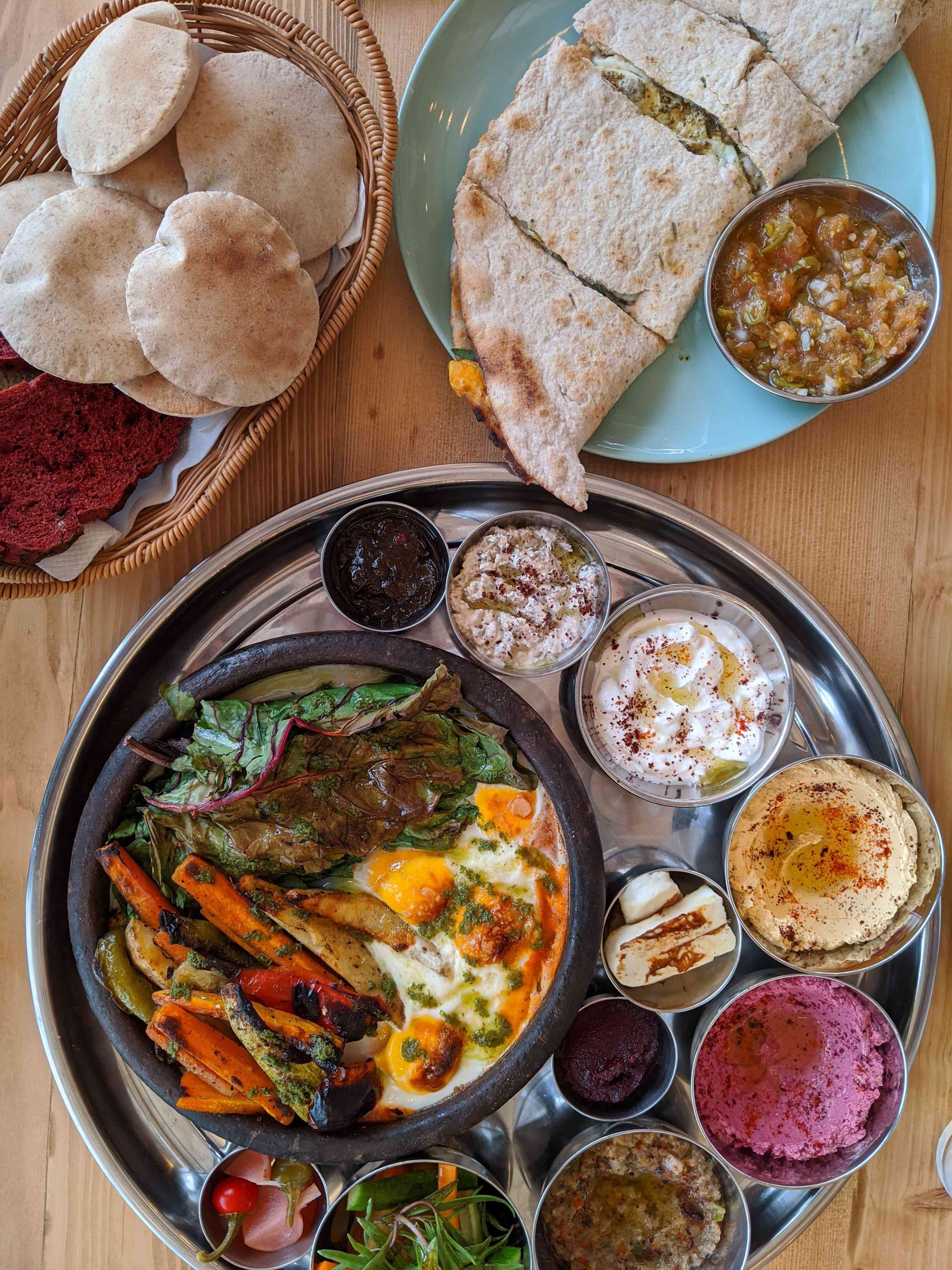 table of food with a basket of white flat breads; a folded,stuffed pita; and a metal tray with a bowl of vegetables and smaller bowls of different hummuses
