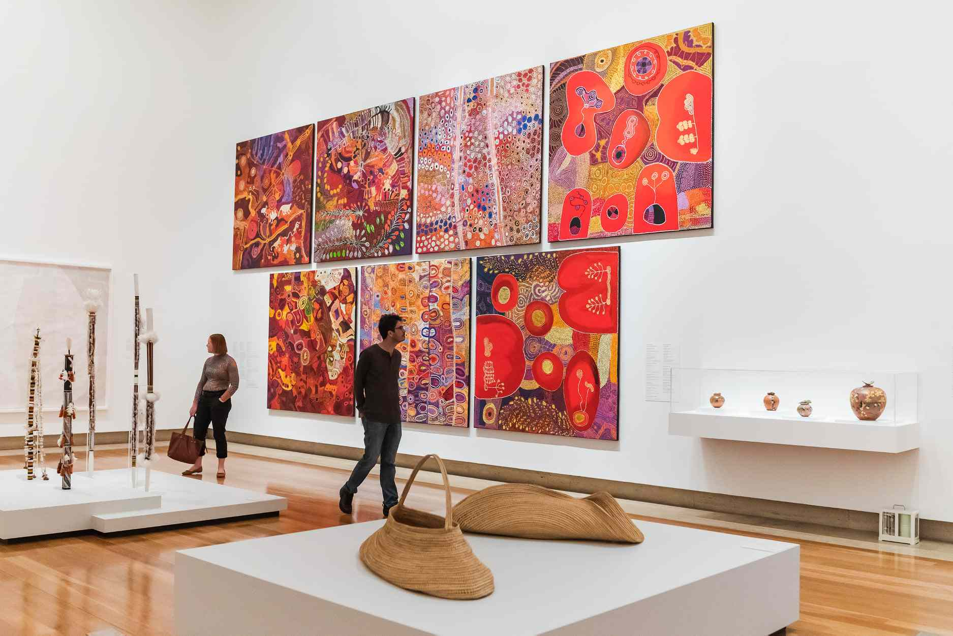 Two people walking in front of Seven large square red paintings on gallery wall
