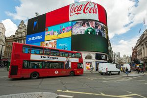 The iconic Regent LCD screens with tourists and a red bus passing by in Piccadilly Circus late in the day.