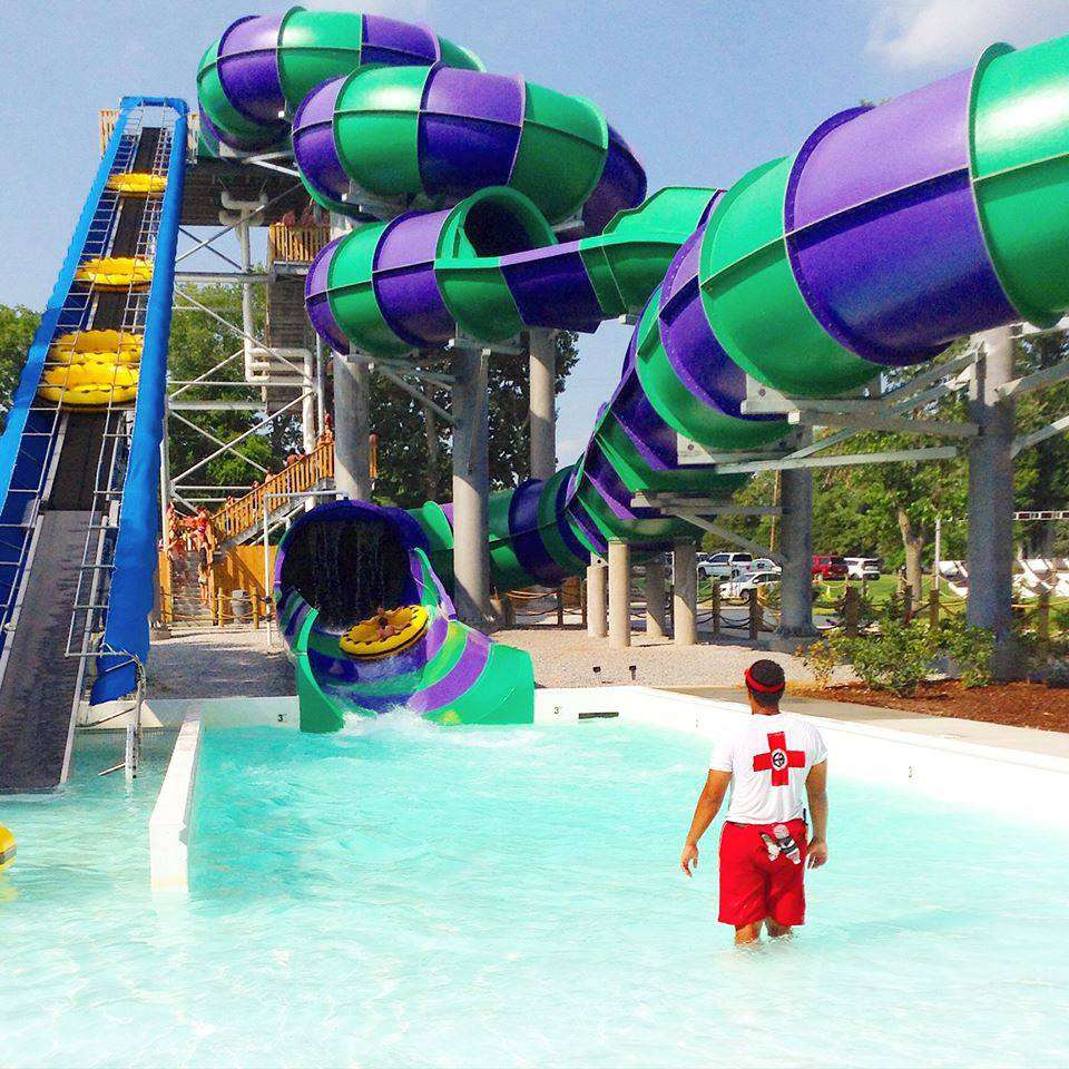 Lifeguard standing at the end of a purple and teal, twisting waterslide