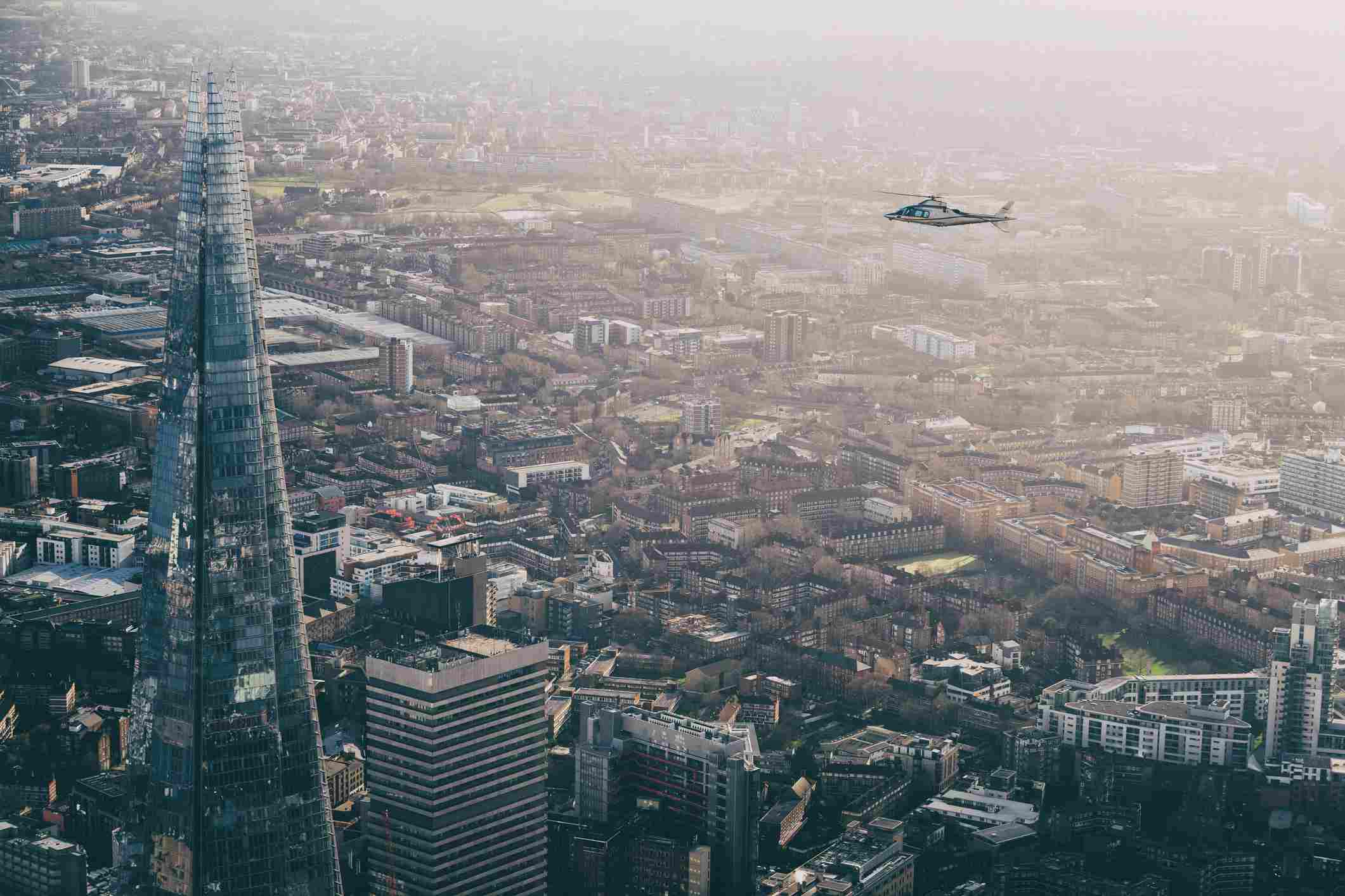 An A-109 helicopter dwarfed by the impressively large building that is The Shard in London.