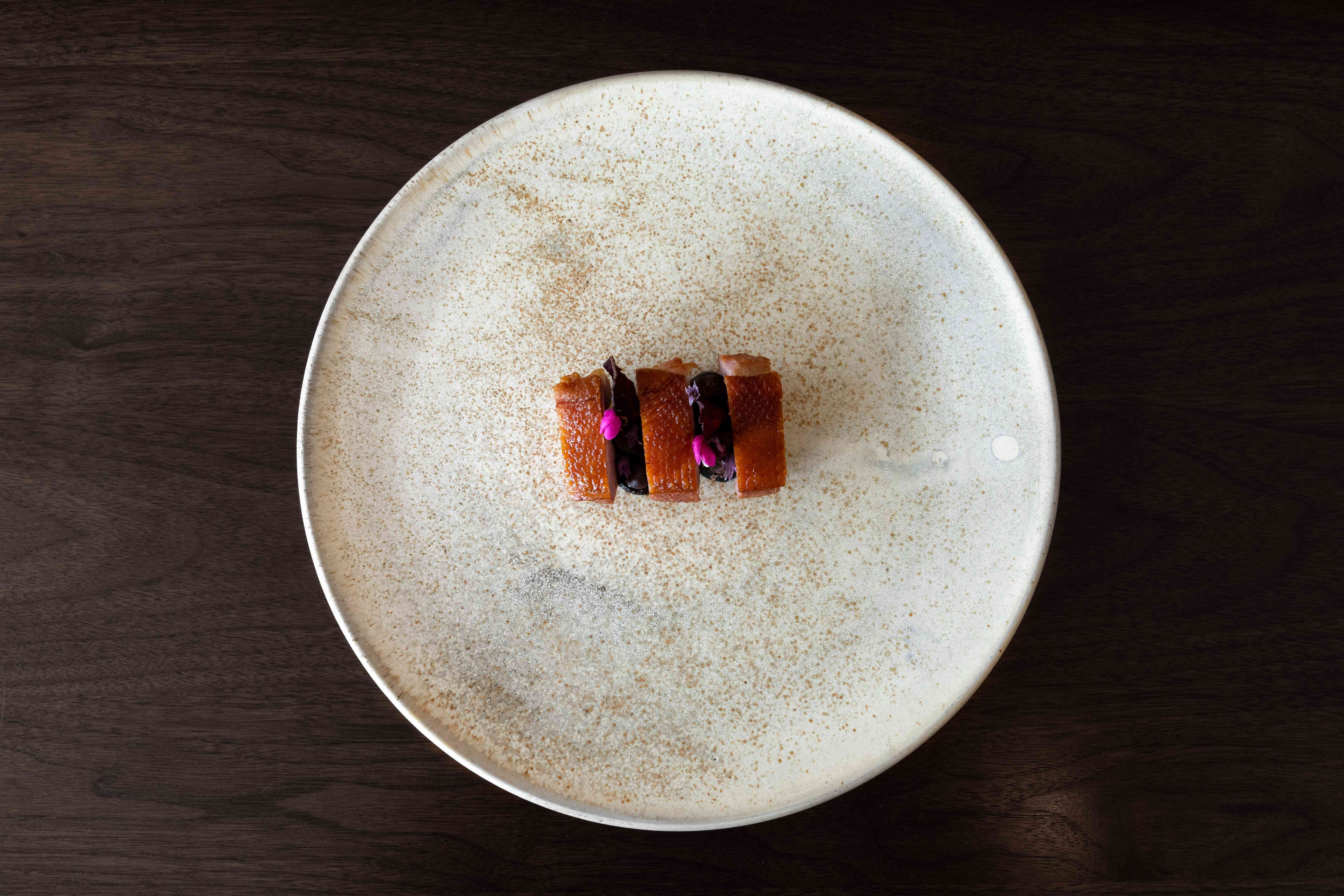 Duck and blueberry amuse bouche on a large round plate