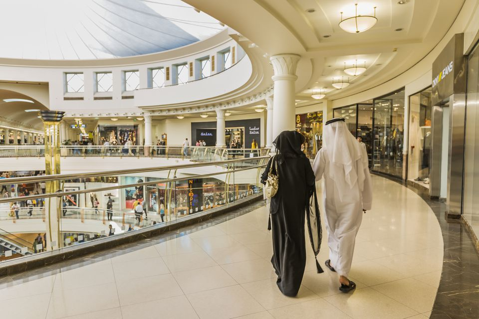 Arab couple walking around a mall.