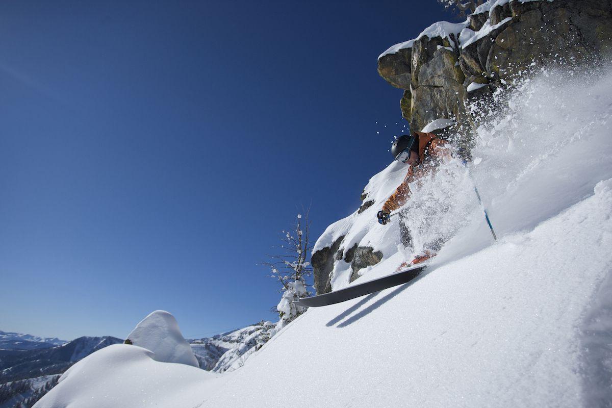A skier shreds through deep snow with a rocky background