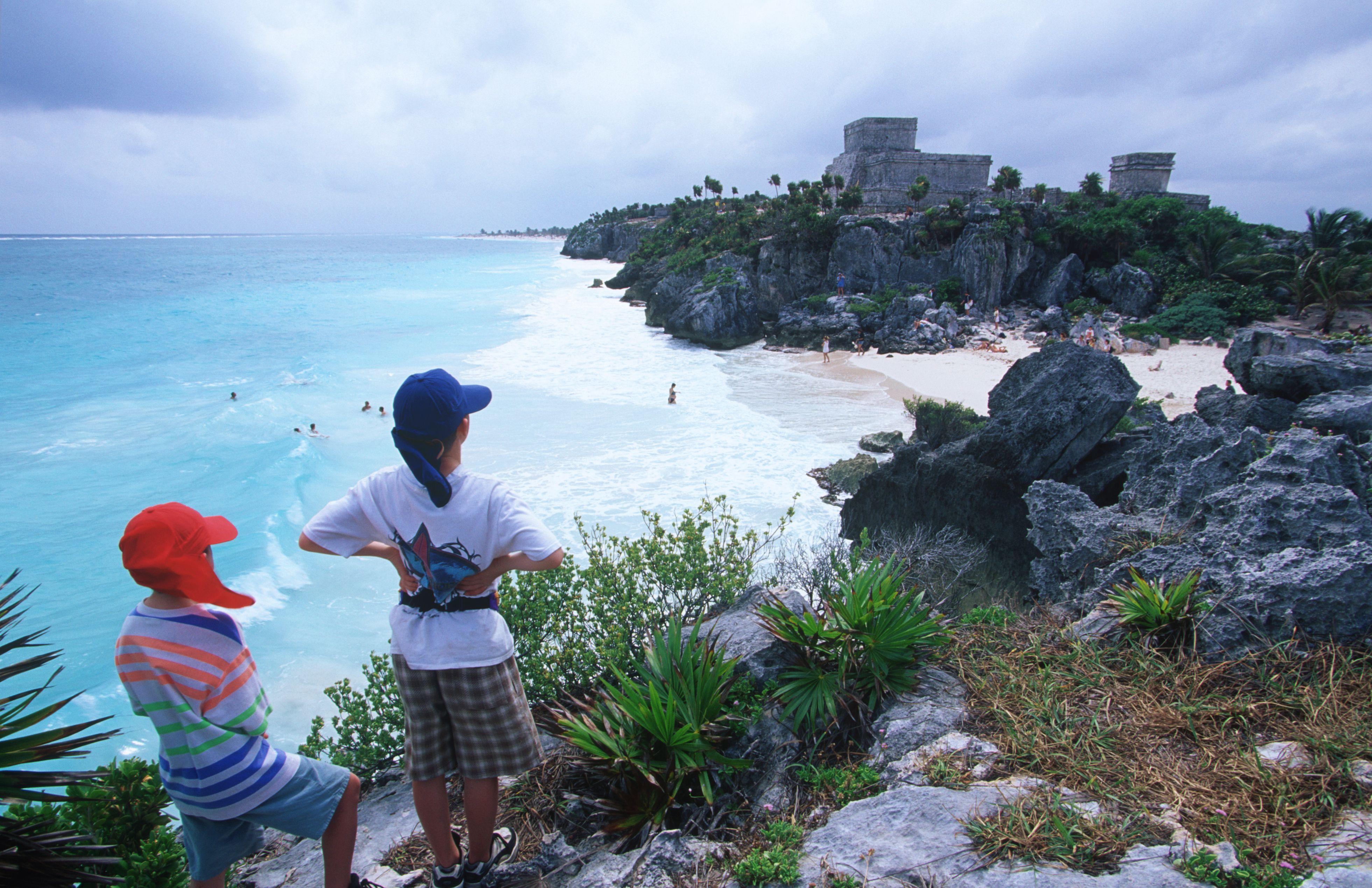Mexico, Yucatan Peninsula, boys on vista overlook Tulum, Mayan ruin by the Carribean sea