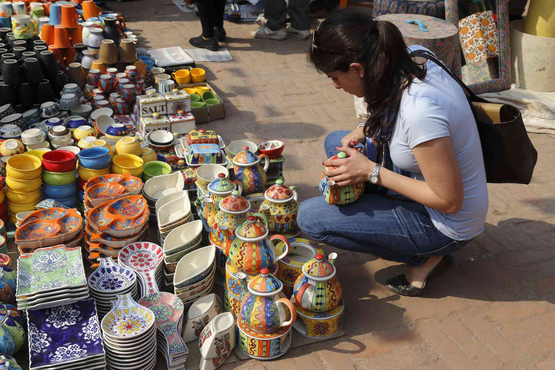 Young woman shopping for crockery and tea pots at Dilli Haat crafts bazaar.
