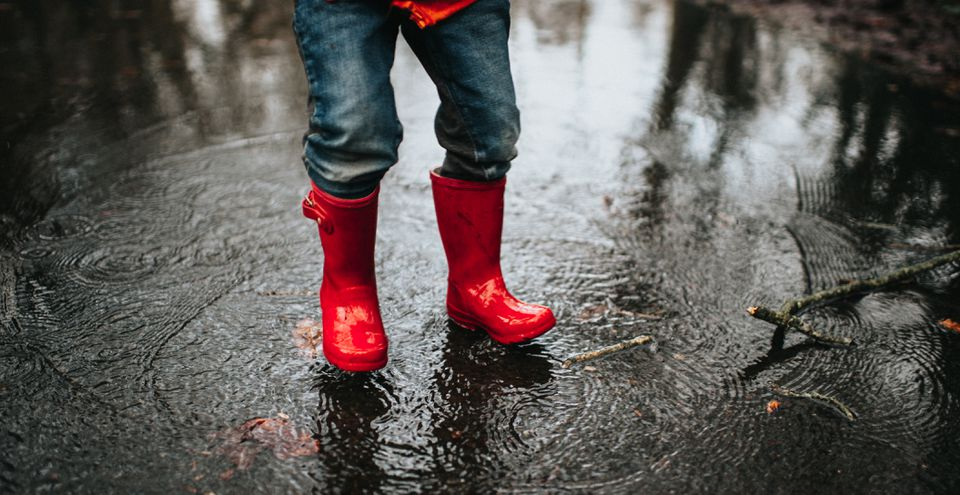a child jumping in a big puddle