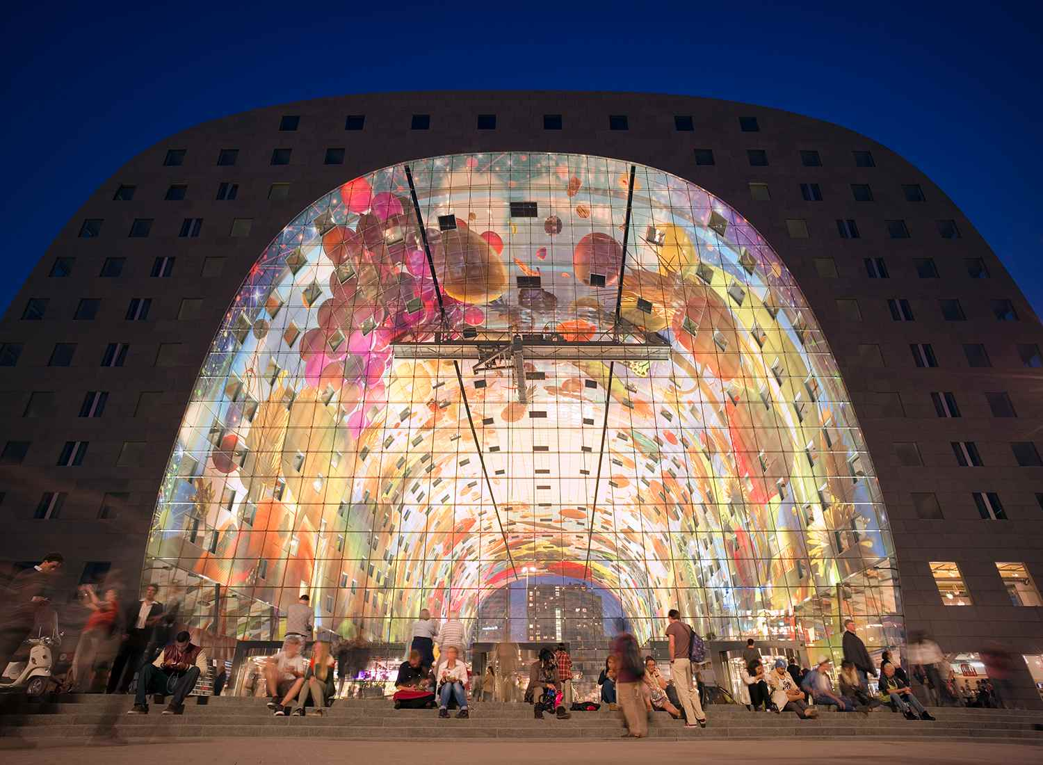 People in front of the Markthal, Rotterdam at dusk.