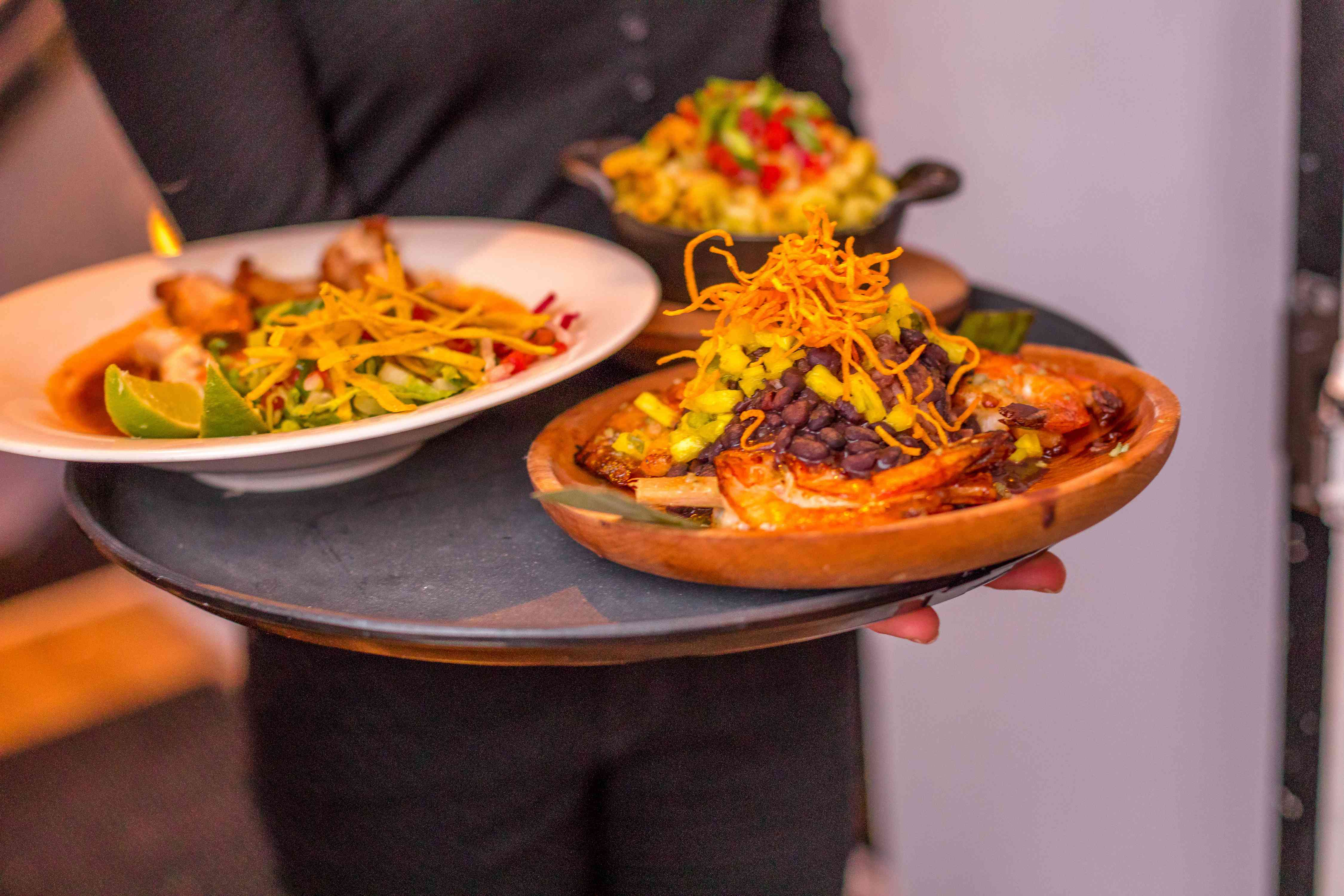 Serve holding a tray of three small plate dishes from Corto Lima