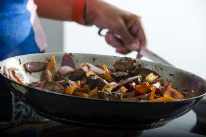 woman Preparing Peruvian salted loin in a wok