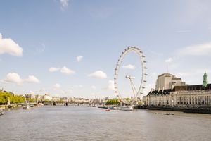 Large white ferris wheel on the right side of a wide river with a pale blue sky and several clouds