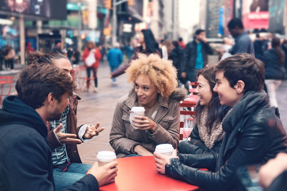 Group of friends in Time Square drinking coffee