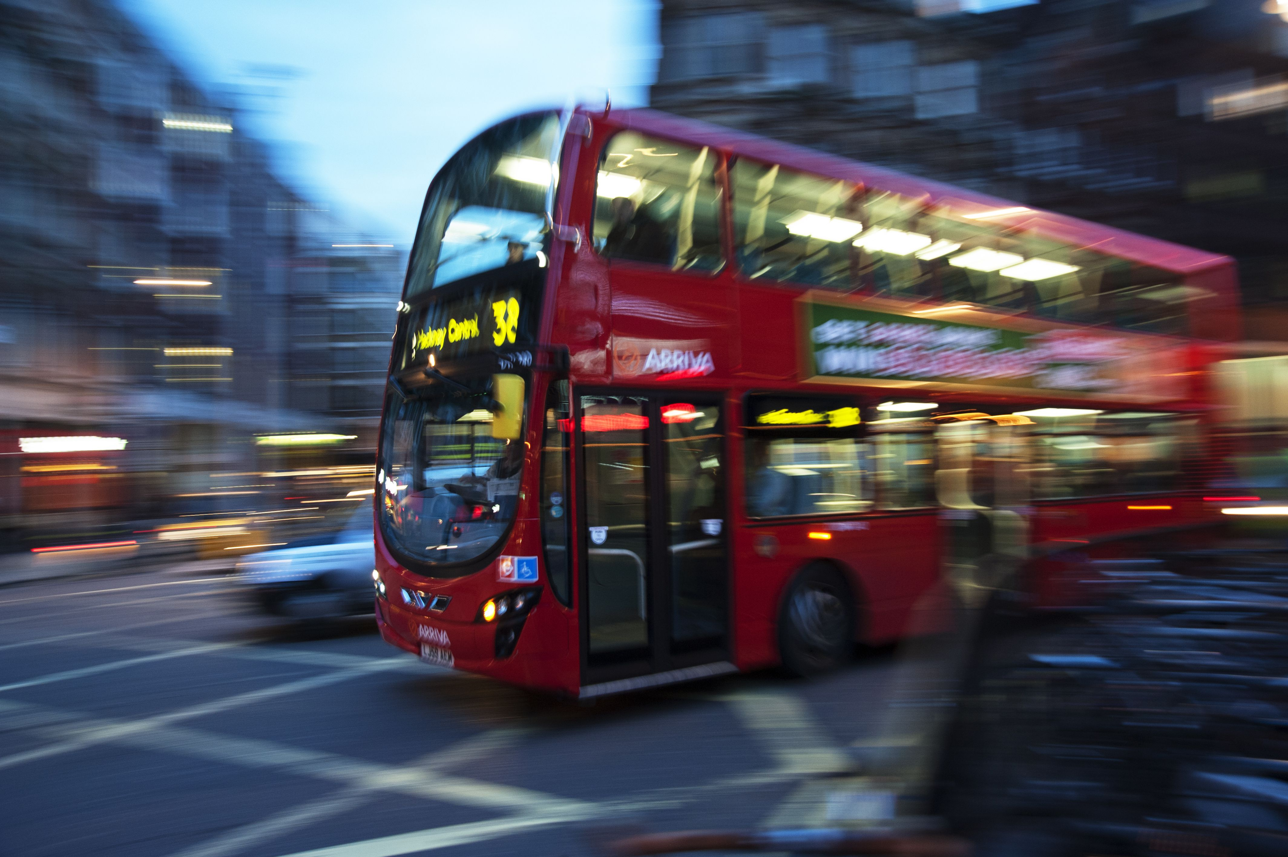autobús número 38 de Londres doblando una esquina en St Giles Circus al anochecer