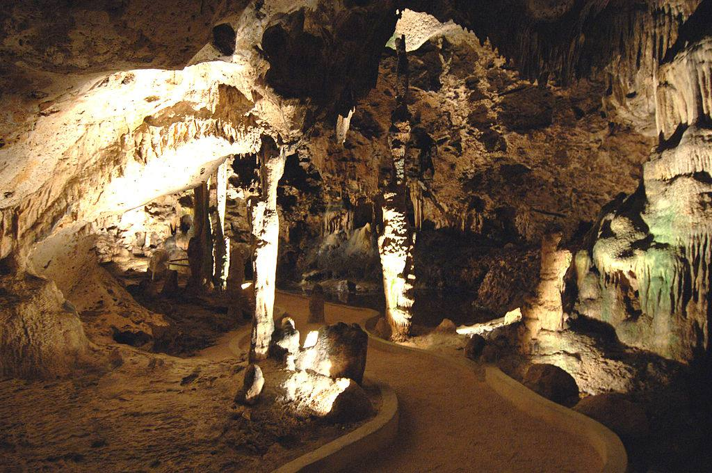 Inside of Hato Caves in Curaçao with a walking path and many stalagmites and stalactites illuminated by inset bulbs.