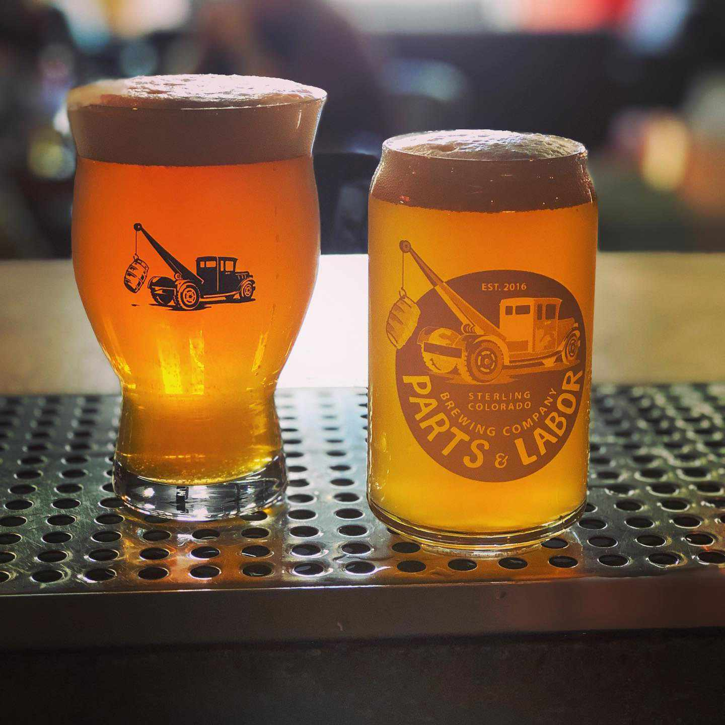 Filled pint glasses branded with Parts & Labor logos